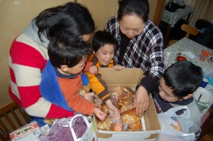 The children rejoicing over the box of bread products donated by a bakery in Niigata