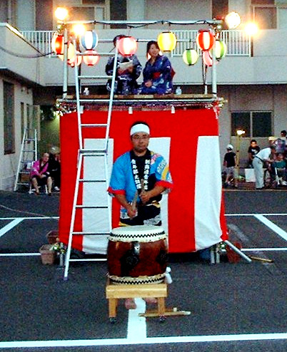 Man beating a drum called taiko in Japanese. In the back of him is the elevated stage that Manami was standing on.
